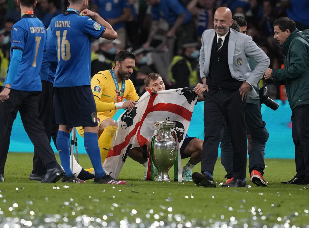 Salvatore Sirigu of Italy (C-L) and Nicolo Barella (C-R) of Italy celebrate with the trophy and a flag of Sardinia after the UEFA EURO 2020 final between Italy and England in London.