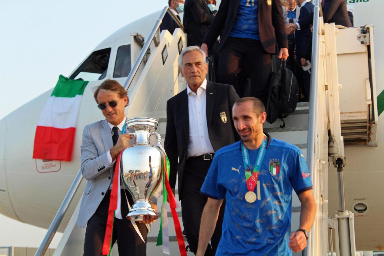 Giorgio Chiellini (R) and head coach Roberto Mancini (L) carry the European Championship trophy as the Italian football team returns from London after winning the UEFA EURO 2020 championship, at Rome's Leonardo Da Vinci airport in Fiumicino