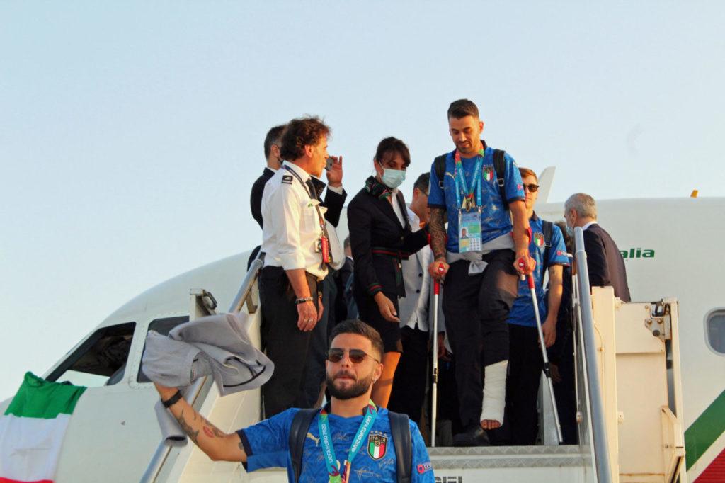 Italian players Lorenzo Insigne (front) and Leonardo Spinazzola (C, rear) at Rome's Leonardo Da Vinci airport in Fiumicino